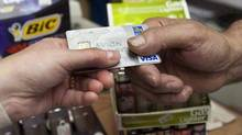 A consumer pays with a credit card at a store in Montreal in 2010. (Ryan Remiorz/The Canadian Press)