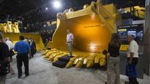 Dmitry Golitsyn of Moscow stands in a new latch free dipper at the Caterpillar booth during MINExpo International 2012 trade show at the Las Vegas Convention Center, in this September 24, 2012 file photo. (STEVE MARCUS/REUTERS)