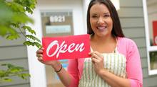 A small-business owner holds up an OPEN sign. (Morgan Lane Studios/Getty Images/iStockphoto)