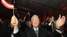 "Austrian-Canadian businessman and billionaire Frank Stronach of ""Team Stronach"" waves an Austrian flag during his final election rally on March 1, 2013. Mr. Stronach's party won 11.3 per cent of the vote in the state of Carinthia and around 9.7 per cent in Lower Austria. (HEINZ-PETER BADER/REUTERS)"