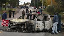 A burned police vehicle is seen in Rexton, N.B., as police began enforcing an injunction to end an ongoing demonstration against shale gas exploration in eastern New Brunswick on Thursday, Oct.17, 2013. (Andrew Vaughan/THE CANADIAN PRESS)