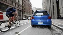 A cyclist passes a car parked in the bike lane on Richmond St. West just west of Bay St. on July 25, 2016 in Toronto. (Fred Lum/The Globe and Mail)