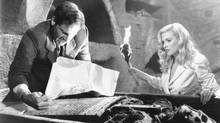 """Indiana Jones and the Last Crusade Indiana Jones (Harrison Ford) and Dr. Elsa Schneider (Alison Doody) search for clues about the location of the Holy Grail in Paramount's """"Indiana Jones and the Last Crusade."""" The Lucasfilm Ltd. production was directed by Steven Spielberg. (1989 Photo by Murray Close/Paramount)"""