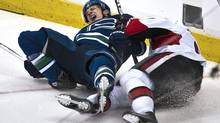 Vancouver Canucks Keith Ballard reacts after his leg twists the wrong way after colliding with Ottawa Senators Milan Michalek during the first period of their NHL hockey game in Vancouver, British Columbia February 7, 2011. (ANDY CLARK)