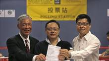 From right to left, Occupy Central co-organizer Chan Kin-man, Benny Tai and Chu Yiu-ming, pose at a polling center with a ballot for an unofficial referendum in Hong Kong Sunday, June 22, 2014. More than 700,000 people have voted in an unofficial referendum on democratic reform organized by the Occupy Central with Love and Peace movement that has alarmed Beijing and sets the stage for a possible showdown with the government, with mass protests aimed at shutting down the Chinese capitalist enclave's financial district. (AP Photo/Vincent Yu) (Vincent Yu/AP)