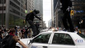Protestors jump on a police car in Toronto's financial district as anti G20 deomonstrators clash with police as the G20 summit commences on Saturday, June 26, 2010.
