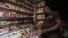 In this photo taken on Feb. 5, 2014, a man arranges Nollywood DVDs in a shop in Lagos, Nigeria. The country's film industry has been newly estimated to be worth $6-billion, part of a recalculation of GDP that makes Nigeria the largest economy in Africa. (Sunday Alamba/The Associated Press)