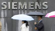 People covered with umbrellas walk next to a Siemens building in Munich November 13, 2008. (MICHAELA REHLE/MICHAELA REHLE/REUTERS)