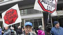 A man holds up signs during a demonstration outside Bombardier's head office in Montreal on Sunday. Exchanges on Bombardier remain heated in Ottawa and Quebec City as opposition parties continue to press the governing federal and Quebec Liberals to demand the company repeal its pay increases. (Graham Hughes/THE CANADIAN PRESS)