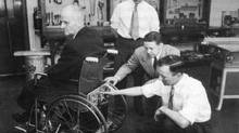 In 1955, George Klein, at back, and colleagues from the National Research Council of Canada and the Department of Veterans Affairs, inspect the prototype for an electric wheelchair. (NRC)