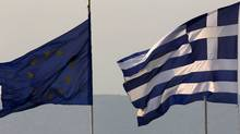 A Greek (R) and an EU flag fly over Greece's Finance Ministry in Athens. (YANNIS BEHRAKIS/Reuters/YANNIS BEHRAKIS/Reuters)