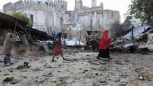 Somali women walk past the site of a deadly blast in Mogadishu April 14, 2013. At least 19 people were killed in the Somali capital on Sunday in bomb attacks carried out by militants linked to al Qaeda and subsequent gun battles with the al Shabaab fighters, breaking a fragile return to peace in Mogadishu. (OMAR FARUK/REUTERS)