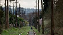 A woman walks across an abandoned rail line that runs through the Arbutus corridor in Vancouver, B.C., on Monday March 7, 2016. (DARRYL DYCK/THE GLOBE AND MAIL)