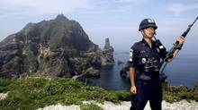 A South Korean police officer stands guard on Dokdo/Takeshima. (YONHAP/REUTERS)