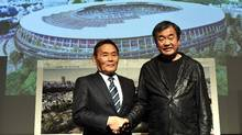 This file picture taken on December 22, 2015 shows Japan Sports Council (JSC) president Kazumi Ohigashi shaking hands with architect Kengo Kuma during a press conference announcing the new design of the national stadium in Tokyo. (TOSHIFUMI KITAMURA/AFP/Getty Images)