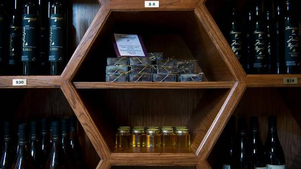 Harvested wildflower honey and various wines for sale in honeycomb-shaped shelves at Rosewood Estates Winery in Beamsville, July 25, 2012.