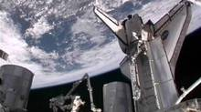 The space shuttle Atlantis is seen docked to the International Space Station with the Earth in the background in this image from NASA TV July 17, 2011. (NASA TV/REUTERS)