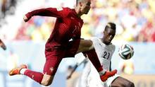 Portugal's Cristiano Ronaldo (L) fights for the ball with Ghana's John Boye during their 2014 World Cup Group G soccer match at the Brasilia national stadium in Brasilia June 26, 2014. (UESLEI MARCELINO/REUTERS)