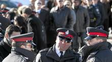 Police Officers wait in line at a funeral home in Toronto on Sunday January 16, 2011, as they wait to pay their respects to Sergeant Ryan Russell. Sgt. Russell was killed after trying to stop a man driving a stolen snowplow through the city early Wednesday morning, striking vehicles and nearly hitting people. (Chris Young/Chris Young for The Globe and Mail)