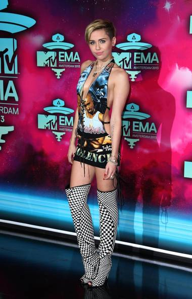 First stop: Amsterdam, where energetic pop tartlet Miley Cyrus wowed fans on the red carpet at the MTV Europe Music Awards with her funky T-shirt dress featuring the faces of dead rappers Tupac Shakur and Biggie Smalls (Joel Ryan/AP)