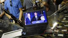 Gun shop customers listen to live streaming video of an announcement about gun control by U.S. President Barack Obama at the Bullet Hole gun shop in Sarasota, Fla., Jan. 16, 2013. (BRIAN BLANCO/REUTERS)