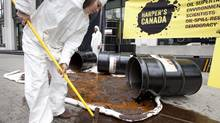 A member of Greenpeace cleans up a mock oil spill outside the Enbridge Northern Gateway pipeline office in downtown Vancouver, Wednesday, June 13, 2012. The mock spill was set up by Greenpeace to show the risks of spills similar to the recent one outside of Red Deer Alberta. (JONATHAN HAYWARD/THE CANADIAN PRESS)