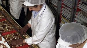 Three employees sort chocolates into boxes at the Lindt and Spruengli chocolate factory in Kilchberg, Switzerland, June 19, 2003.