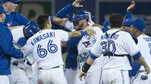 Toronto Blue Jays' Melky Cabrera celebrates with teammates after knocking in the winning run (Darren Calabrese/THE CANADIAN PRESS)