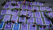 A woman places roses on photos of murdered or missing women after the Missing Women Coalition met with government officials, Nov. 25, 2013. (Darryl Dyck For The Globe and Mail)
