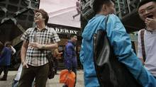 Mainland Chinese visitors stand outside a Burberry store at Tsim Sha Tsui shopping district in Hong Kong January 18, 2013. (Bobby Yip/REUTERS)
