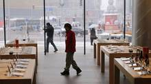 A staff walks inside an empty Apple store during the release of iPhone 5 in Beijing's Wangfujing shopping district, December 14, 2012. Recent slide in company's may be linked to new technology being tested by China's top telecoms carrier. (PETAR KUJUNDZIC/REUTERS)