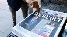 A man takes a copy of the London Evening Standard with the front page reporting the resignation of British Prime Minister David Cameron and the vote to leave the EU in a referendum. (Leon Neal/AFP/Getty Images)