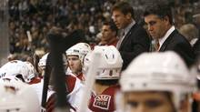 Phoenix Coyotes head coach Dave Tippett stands behind his team against the Los Angeles Kings during the first period of their game Saturday in Los Angeles. (Danny Moloshok)