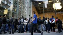 Customers wait in line to purchase the new Apple Inc. iPhone 5 in New York, U.S., on Friday, Sept. 21, 2012. Apple Inc. is poised for a record iPhone 5 debut and may not be able to keep up with demand as customers lined up in Sydney, Tokyo, Paris and New York to pick up the latest model of its top-selling product. Photographer: Victor J. Blue/Bloomberg New York customers line up for a new iPhone, which Apple developed through a mix of building, borrowing and buying. (Victor J. Blue/Bloomberg)