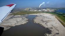 Aerial image of an oil sands processing facility and associated tailings pond (below aircraft). The wing of the aircraft used to make the measurements in this study is shown in the image. (Environment and Climate change Canada)