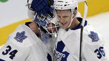 Toronto Maple Leafs goalie James Reimer (34) celebrates with teammate Carl Gunnarsson (36), from Sweden, after defeating the Montreal Canadiens 4-3 in their National Hockey League season opener Tuesday, October 1, 2013 in Montreal. Reimer is expected to start in Toronto's home opener against Ottawa on Saturday. (RYAN REMOIRZ/THE CANADIAN PRESS)