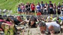 TORONTO: June 19, 2011 -- Racers trudge through mud under barbed wire during the Spartan Race at Kelso Quarry in Milton. Photo by Della Rollins for the Globe and Mail. (Della Rollins/Della Rollins for The Globe and Mail)
