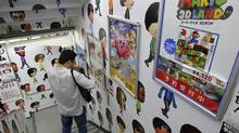 A man walks down the stairs covered with Nintendo Wii characters at an electronics retailer in Tokyo, Thursday, Oct. 27, 2011. (Koji Sasahara/AP)