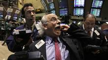 Trader Peter Tuchman, centre, works on the floor of the New York Stock Exchange, March 13, 2012. (Richard Drew/Richard Drew/AP)