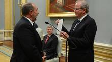 Infrastructure Minister Denis Lebel, left, is sworn as Stephen Harper looks on. (Sean Kilpatrick/THE CANADIAN PRESS)