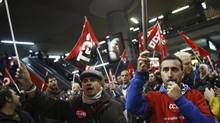 Picketers from workers' and trade unions shout slogans at Atocha rail station during a 24-hour nationwide general strike in Madrid, Nov. 14, 2012. Spanish and Portuguese workers staged the first co-ordinated strike across the Iberian peninsula on Wednesday, shutting down transport, grounding flights and closing schools to protest austerity measures and tax hikes. (PAUL HANNA/REUTERS)