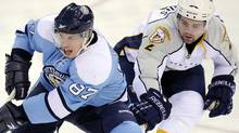 Pittsburgh Penguins' Sidney Crosby (87) passes the puck as Nashville Predators defenseman Dan Hamhuis (2) defends during the first period of an NHL hockey game in Pittsburgh, Sunday, Feb. 14, 2010. Nashville won 4-3 in a shootout. (AP Photo/Don Wright) (Don Wright)