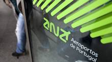 People leave Lisbon's airport by a door decorated with the logo of airport management company ANA Dec. 27 2012. Portugal's government decided to sell the company that runs eight airports in Portugal as part of the effort to deal with the country's financial crisis. (Armando Franca/AP)