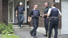 Police leave a house in the west end of Ottawa, Aug. 25, 2010. (Adrian Wyld/THE CANADIAN PRESS/Adrian Wyld)