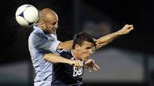 Sporting Kansas City's Aurelien Collin, left, and Vancouver Whitecaps' Sebastien Le Toux collide going after the ball during a soccer match in the Walt Disney World Pro Soccer Classic, Wednesday, Feb. 29, 2012, in Lake Buena Vista, Fla. (John Raoux/AP)