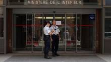 Police officers stand in front of the offices of the judicial police in Nanterre, near Paris, July 1, where former French President Nicolas Sarkozy arrived early Tuesday to be quizzed by investigators. (BENOIT TESSIER/REUTERS)