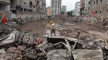A man walks at the site where a Bangladesh garment factory building collapsed on April 24 in Savar, near Dhaka, Bangladesh, killing more than 1,100 people. Toronto-based Loblaw will compensate victims of the collapse. The factory produced Loblaw's Joe Fresh line of clothing. (A.M. Ahad/AP)