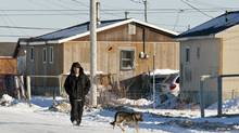 A man walks down the street in Attawapiskat, Ont., on Nov. 29, 2011 (Adrian Wyld/The Candian Press)