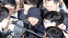 In this Monday, Oct. 31, 2016 photo, Choi Soon-sil, center, is surrounded by media upon her arrival at the Seoul Central District Prosecutors' Office in Seoul, South Korea. South Korean prosecutors requested an arrest warrant Wednesday, Nov. 2, for the longtime friend of President Park Geun-hye over allegations of influence-peddling and other activities that have triggered a huge political scandal that threatens Park's leadership. (Lee Jin-man/AP)