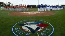 A woman sings the national anthems as the Toronto Blue Jays host the Baltimore Orioles during MLB Grapefruit League baseball action in Dunedin, Fla., on Sunday, Feb. 24, 2013. (Nathan Denette/THE CANADIAN PRESS)